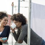 young mixed raced couple is drinking tea on roof top